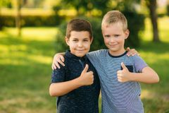 Two bothers spend time in park. They have fun and some relax befour school.  stock image