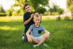 Two bothers spend time in park. They have fun and some relax befour school.  royalty free stock photo
