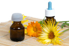Two bottle and calendula flowers on bamboo plate Royalty Free Stock Images