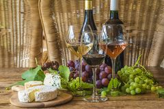 Two bottle of wine and three glasses of white, pink and red wine. S, various of french cheeses on vintage woodet table with wicker chairs royalty free stock photography