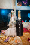 Two bottles of champagne decorated as a bride and groom standing Stock Photo
