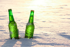 Two bottles of cold beer on the snow at sunset Stock Photo