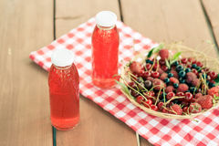 Two bottles of cold stewed fruit from assorted berries. Two bottles of a cold stewed fruit from assorted berries Royalty Free Stock Photos