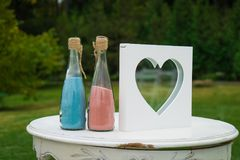 Two bottles with colorfull sand on the table on wedding venue. Close up Stock Image
