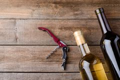 Two bottles and corkscrew. On a wooden table. White and red wine. Horizontal still life with space to insert your content royalty free stock image