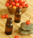 Two bottles of essence oil, stones and fresh cher Royalty Free Stock Image