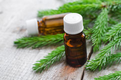 Two bottles of essential oil and fir branches. Aromatherapy and spa products Royalty Free Stock Image