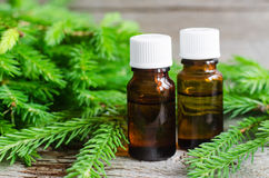 Two bottles of essential oil and fir branches. Aromatherapy and spa products Royalty Free Stock Photo