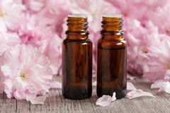 Two bottles of essential oil with pink japanese cherry blossoms in the background stock image