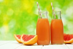 Two bottles of grapefruit juice with defocused outdoor background Royalty Free Stock Photos