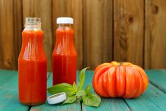 Two bottles of homemade ketchup with fresh green basil and red o Stock Photos