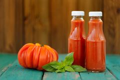 Two bottles of homemade ketchup with fresh green basil and red o Royalty Free Stock Image