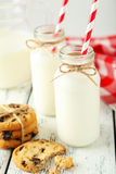 Two bottles of milk with striped straws and cookies on the white wooden background Royalty Free Stock Photos