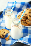 Two bottles of milk with striped straws and plate of cookies Stock Image