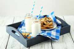 Two bottles of milk with striped straws and plate of cookies on the white wooden background Stock Image