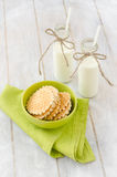 Two bottles of milk and waffles. Two bottles of milk on the old retro kitchen table with waffles in a ceramic bowl on a green table napkin Royalty Free Stock Photos