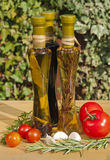 Oil and vinegar bottles in a sunny garden. Two bottles of oil and a bottle of vinegar on a garden table with some tomatoes, garlic and rosemary royalty free stock photo