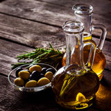 Two  bottles of olive oil, olive in a bowl and herbs on a wooden table. Stock Photos