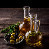 Two  bottles of olive oil, olive in a bowl and herbs on a wooden table. Stock Images