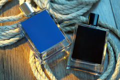 Two bottles of perfume for men and rope on woody table. Male beauty concept stock photos