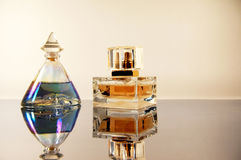 Two bottles perfume on mirror surface Royalty Free Stock Photography