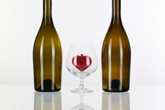 Two bottles and red heart inside a glass of cognac Royalty Free Stock Photography