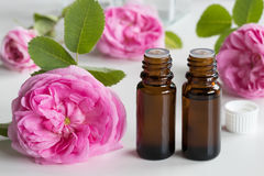Two bottles of rose essential oil with rose flowers in the background stock image