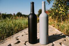 Two bottles stand on a rural road, private vineyards. natural drink. wine stock photo