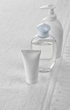Two bottles and tube on white towel Royalty Free Stock Photo