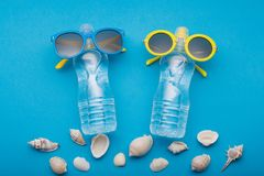 Two bottles of water on a blue background are like people on vacation, bottled glasses, beside scattered seashells, concept. Summer stock images