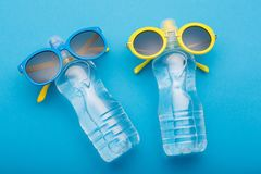 Two bottles of water on a blue background are similar to people sunbathing on the beach, bottled glasses, concept summer. Water royalty free stock photography