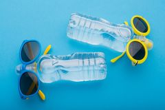 Two bottles of water lie on a blue background, like people sunbathing in the sun, bottles of blue and yellow glasses, concept. Summer, water royalty free stock images