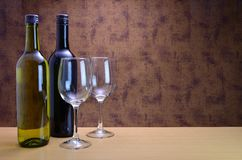 Two bottles of wine. A bottle of red and a bottle of white wine with two empty glasses Royalty Free Stock Photos
