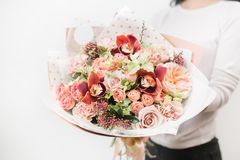 Bouquet of beautiful flowers in women`s hands. Floristry concept. Spring colors. the work of the florist at a flower Stock Photo