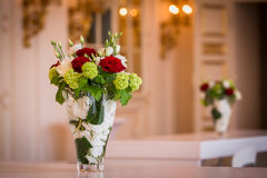Two bouquets of flowers in glass vases. Two identical bouquets of red, green and white flowers in glass vases standing on tables royalty free stock photo