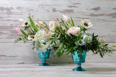 Two bouquets of fresh flowers. Two Bouquets of ranunculus, anemones and other fresh flowers in two blue vases stands on the background of vintage floor Royalty Free Stock Photography