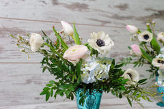 Two bouquets of fresh flowers. Two Bouquets of ranunculus, anemones and other fresh flowers in two blue vases stands on the background of vintage floor Stock Photos