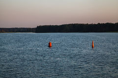 Two bouys in the river. Two red buoys in the blue river. Sunset Royalty Free Stock Photo