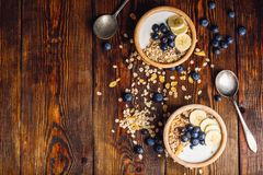 Two Bowl of with Granola, Banana and Blueberry. Two Bowl of Granola, Banana, Blueberry and Greek Yoghurt. Scattered Ingredients on Wooden Table. View from Above royalty free stock photo