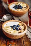 Two Bowl of Granola with Banana and Blueberry. Two Bowl of Granola with Banana, Blueberry and Greek Yogurt for Breakfast. Vertical Orientation royalty free stock photo