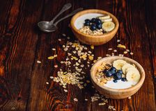 Two Bowl of Granola with Banana and Blueberry. Two Bowl of Granola with Banana, Blueberry and Greek Yogurt for Breakfast. Scattered Muesli on Wooden Table. Copy stock photos