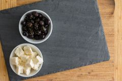 Two bowls of black Mediterranean olives and feta royalty free stock image
