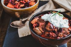 Two Bowls of Borscht Soup with Meaty Chunks of Beef and Sour Cream. Two bowls of Borscht soup with hearty, meaty chunks of beef, root vegetables, cabbage and royalty free stock image