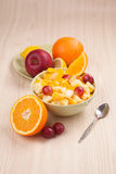 Two bowls with fruit salad on wooden table with half of orange Stock Images