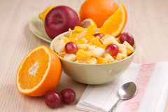 Two bowls with fruit salad on wooden table with half of orange Royalty Free Stock Photos