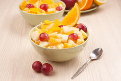 Two bowls with fruit salad on wooden table with spoon Stock Photography