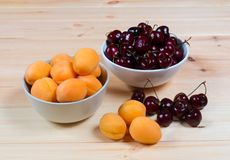 Two bowls full of fresh apricots and cherries berries Stock Image