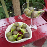Two bowls with green figs on a wet garden table Stock Photos