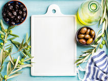 Two bowls with pickled green and black olives, olive tree sprigs, oil in glass bottle, white ceramic board in center Royalty Free Stock Images