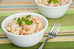 Two bowls of potato salad and a fork. Bowl of potato salad and a fork on green  decorative napkin Stock Photo